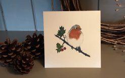 Christmas card robin on holly branch
